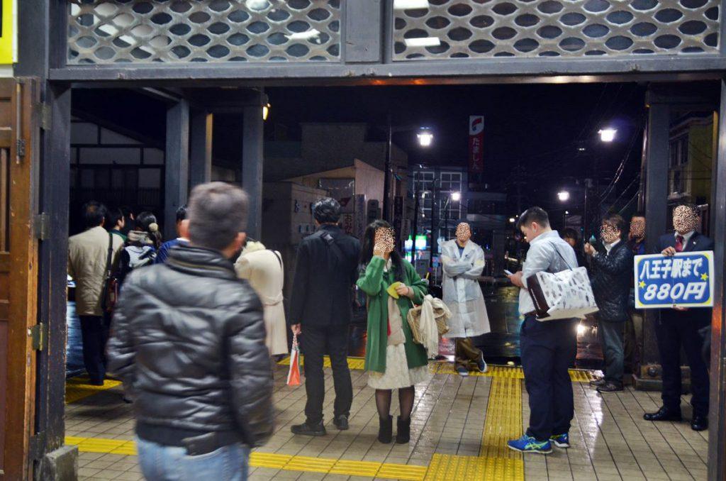 高尾駅で「寝過ごし救済バス」を係員が案内する