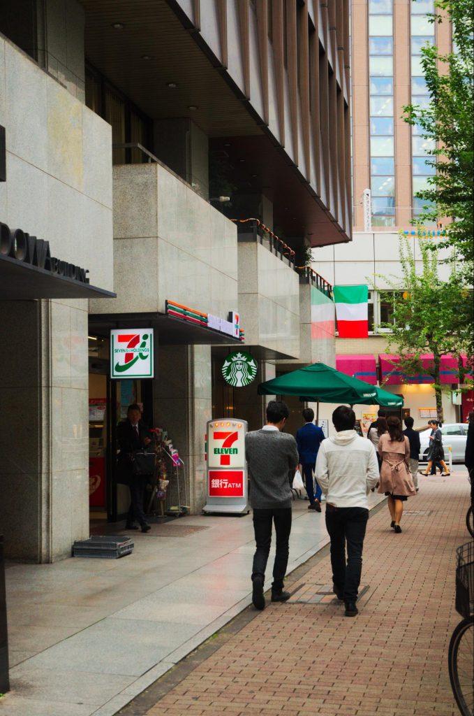 幅の広い看板ではなく「SEVEN-ELEVEn」の表記とロゴ、そしてオレンジ・緑・赤のシンプルな帯があるだけの非常に洗練された外装の店舗である。(撮影:2016年・白井大河)