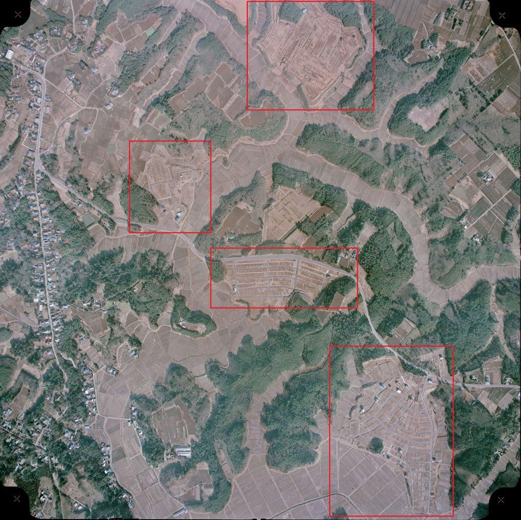 1975年当時の下総町(現成田市)名古屋付近の上空写真。旧来の集落から離れた丘陵上の山林を造成し、いくつもの住宅用地(赤枠内)が開発されている模様が視認できる。(1975年2月撮影・国土地理院航空写真提供サービスを利用して一部加工の上引用)